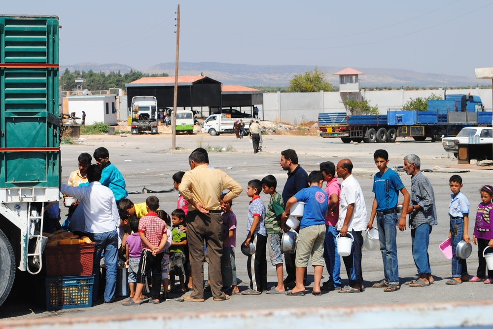 The Foundation for Human Rights and Freedoms and Humanitarian Relief (IHH), a Turkish NGO, provides food to thousands of Syrians stuck on the Syrian side of the Bab-al-Salam border crossing into Turkey. Cross-border aid, without government approval, is co