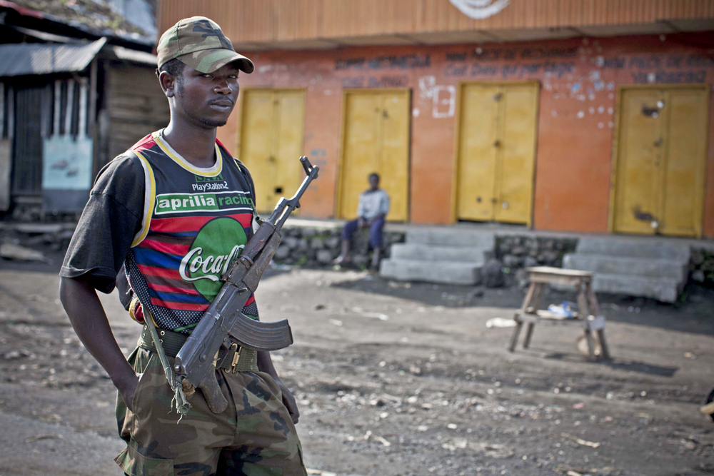 An M23 rebel soldier patrols the town of Sake, Democratic Republic of Congo, which was seized days before. The town was deserted after its capture, but people are slowly returning [November 2012]