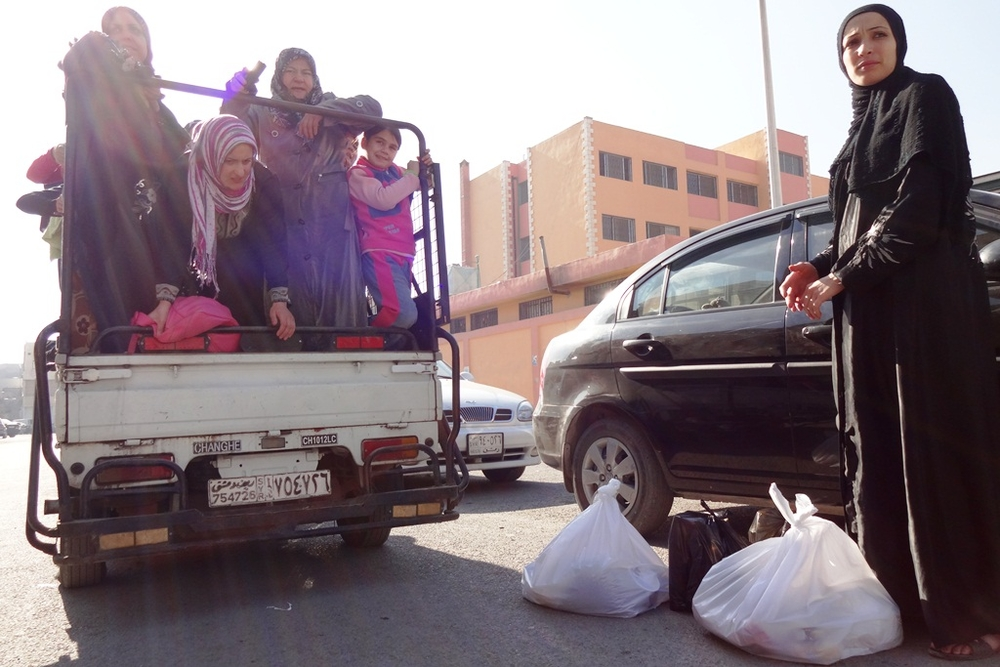 Syrians displaced from Homs, Hama and Rural Damascus, and now living in the capital's suburbs, pack into a mini-truck to come into the city to pick up food aid, mattresses and other supplies from an aid organization