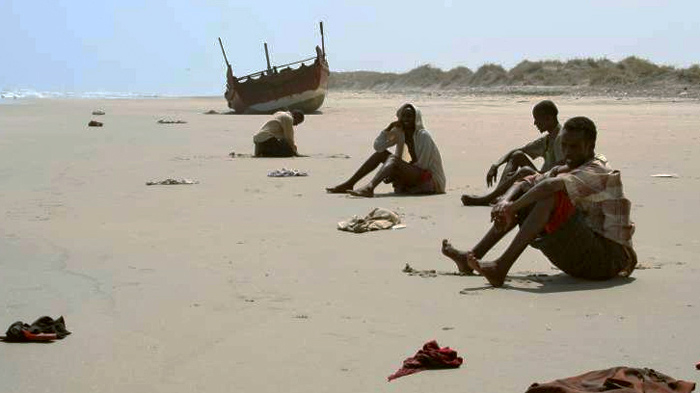 Exhausted survivors of the Gulf of Aden crossing wait for help on a beach in Yemen (file photo)