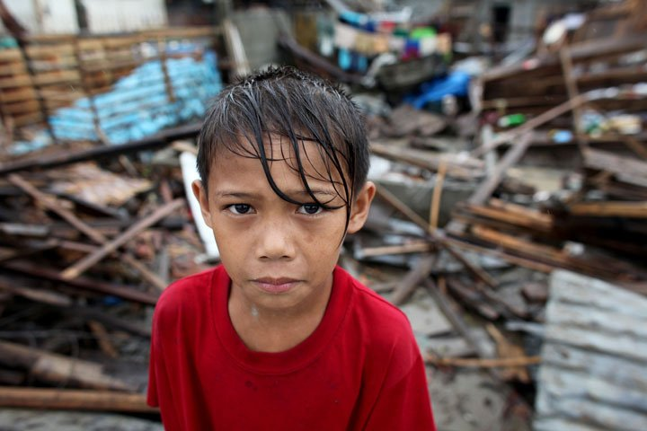 GBoy Quizon, 9, stands amidst the rubble in their village after super typhoon Pablo hit Compostela Valley last December 2012