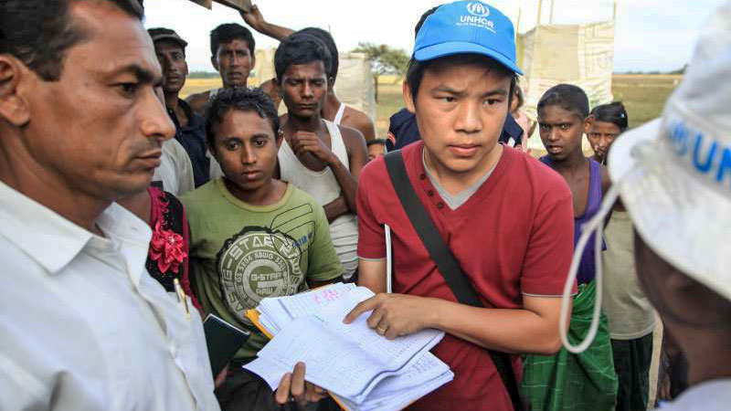 A UNHCR member of staff discusses accommodation with colleagues and displaced people at the Ohn Taw Gyi IDP camp near Sittwe, capital of Rakhine state