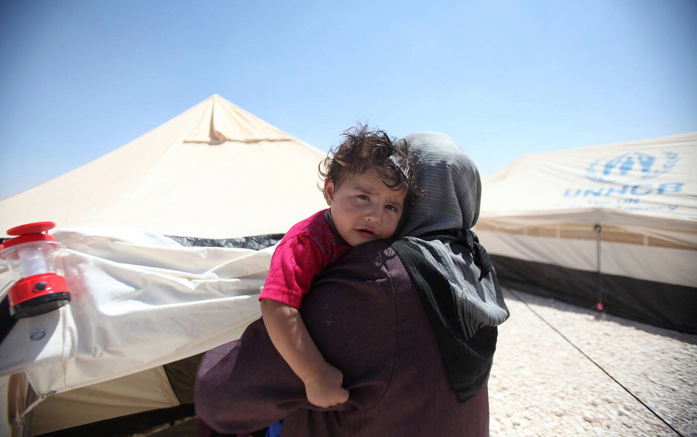 A Syrian refugee woman holds her child in Jordan's Zaátri camp