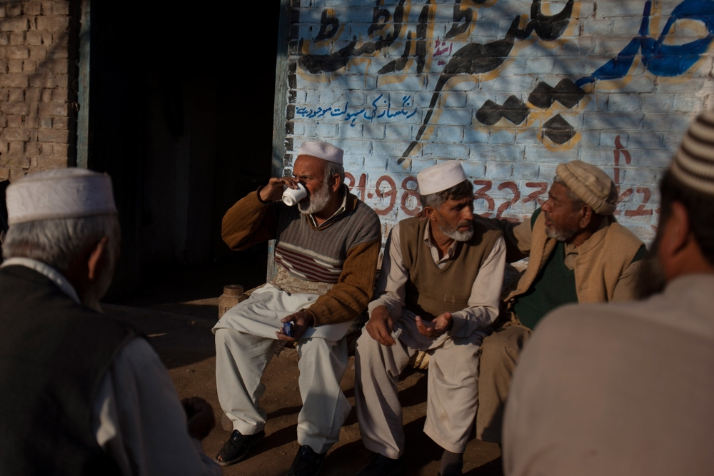 Pakistani men displaced by fighting in the town of Barra in the country's Khyber tribal region drink tea and talk outside a shop in the village of Phandu, Peshawar, Pakistan on Feb. 9, 2013