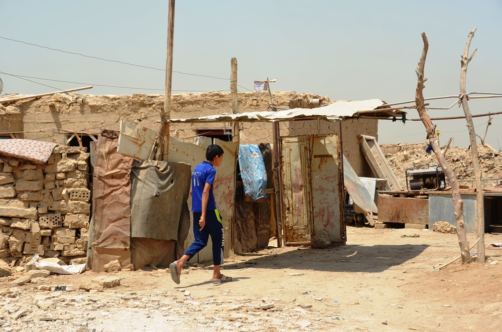 A boy walks past makeshift homes in Al-Rustumiya, an informal settlement for displaced people settlement on the outskirts of the Iraqi capital Baghdad