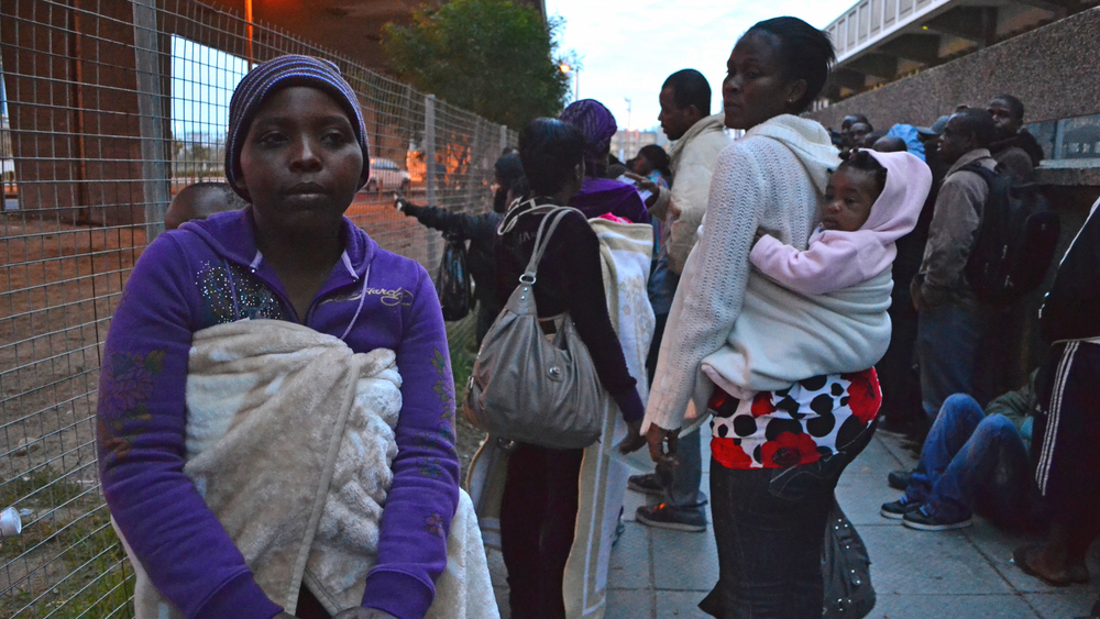 Edeline Kupara, from Zimbabwe, queuing outside the refugee reception office in Cape Town to renew her asylum seeker permit. Asylum seekers like Kupara, who registered at other offices, are not being assisted