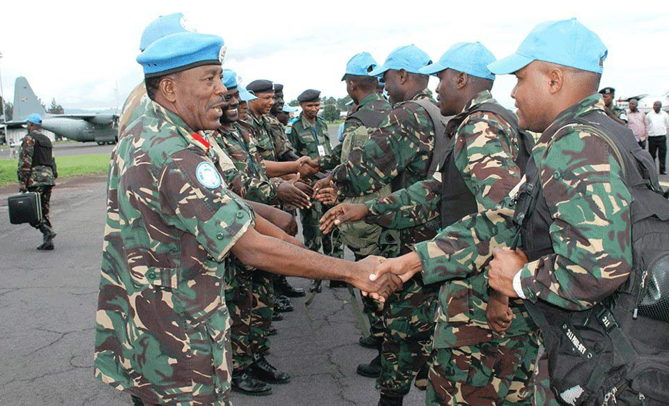 Tanzanian UN Intervention Brigade commander Brig-Gen James Makibolwa shakes hands with Tanzanian troops