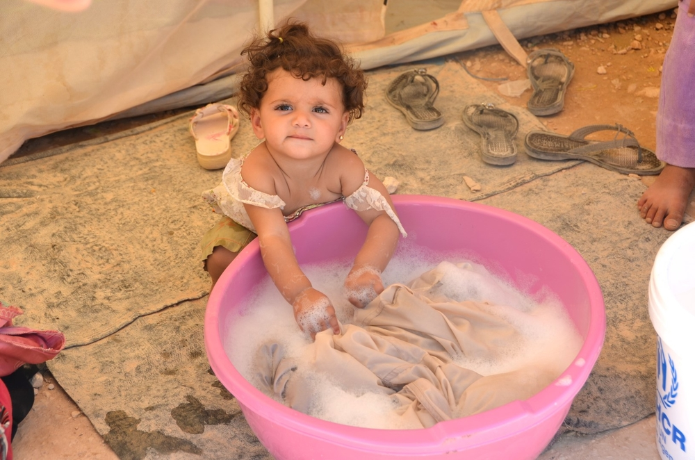 A Syrian refugee child plays with a tub of water in Jordan's Za'atari camp. Many Syrians - both inside and outside their country - cannot access enough clean water or sanitation
