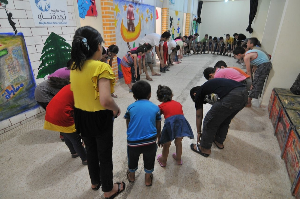 The NGO Najda Now helps children overcome trauma through art and theatre. Here, Najda's office in Lebanon works with refugee children from Syria and Palestine. They are stretching before class