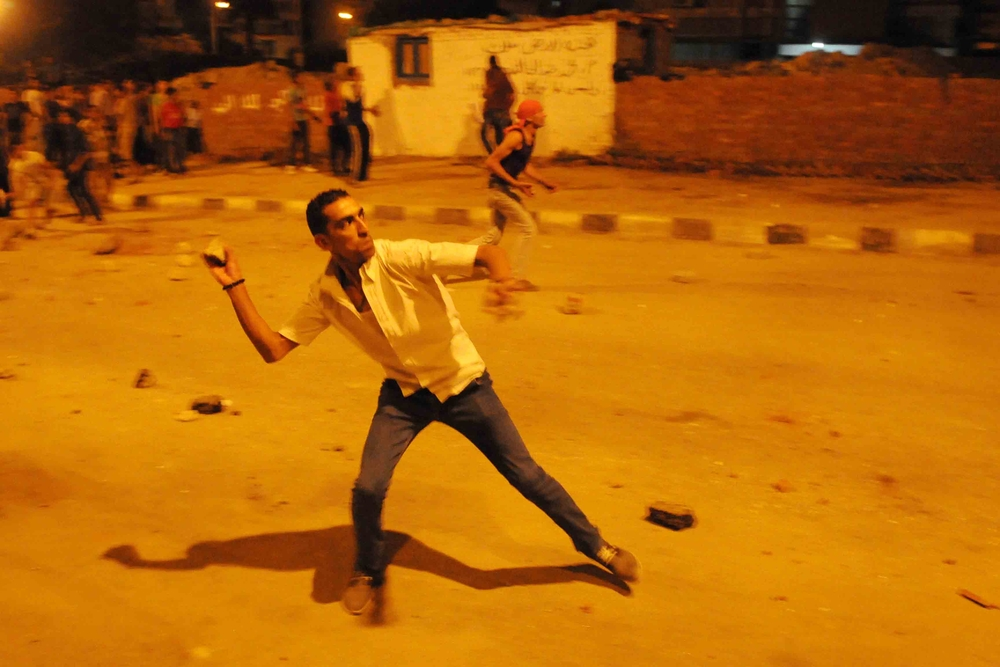 An opponent of the Muslim Brotherhood throws stones at the movement's headquarters of the  in Muqqatam, southeast of Cairo on 30 June, just days before the MB's Mohamed Morsi was ousted as president of Egypt.