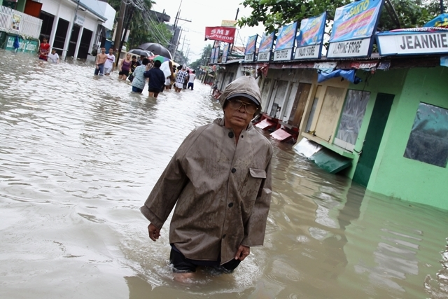 Kawit, Cavite- Residents wade through muddy water was torrential rains caused by Tropical Storm Trami flooded much of Manila and surrounding coastal areas
