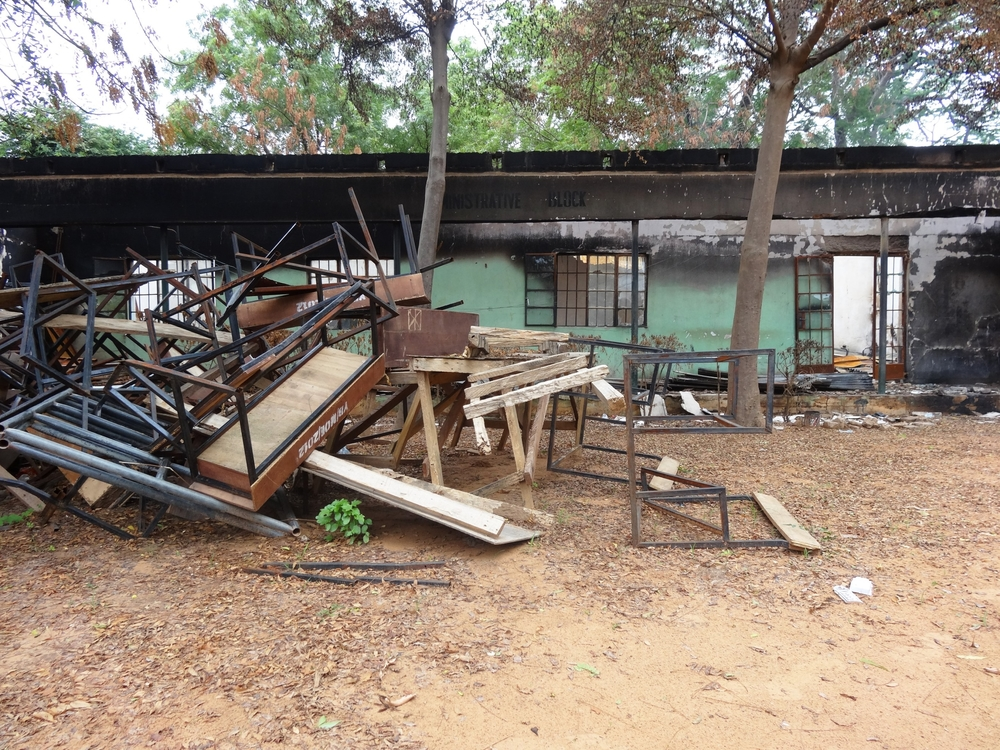 A heap of broken furniture outside burnt classrooms at a  government secondary school Mamudo in Yobe state, northern Nigeria