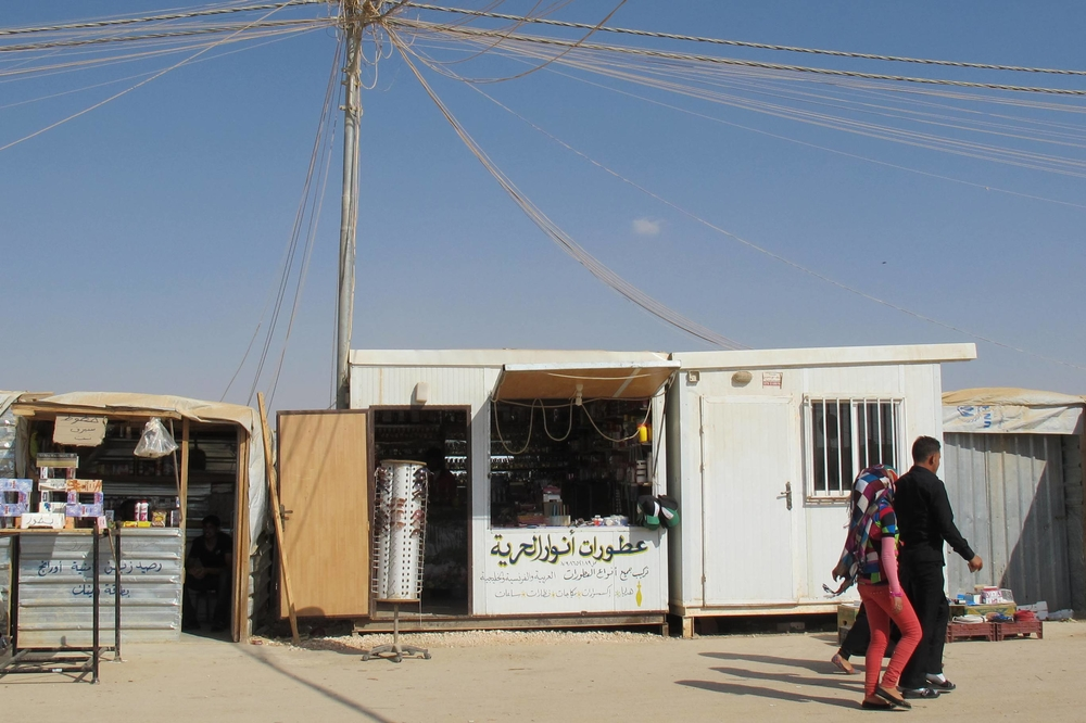 A Syrian refugee in Jordan's Za'atari camp turns his caravan into a shop selling perfumes. A market economy has sprung up in Za'atari camp, now home to some 120,000 Syrians