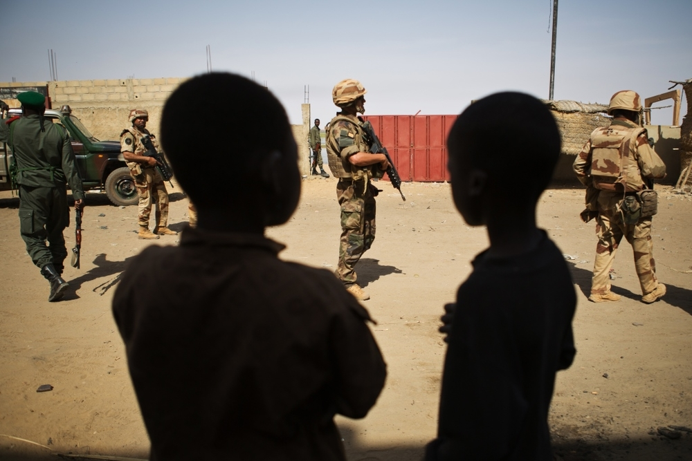 Two Malian boys watch as French and Malian military patrol the market area of downtown Gao, in Gao, Mali, 2 March 2013