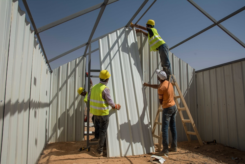 Workers put up specially-designed metal shelters - more resistant to the elements - in Azraq, a new camp for Syrian refugees in the Jordanian desert