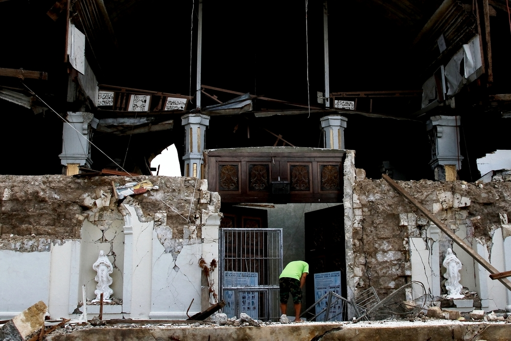 Tubigon, Bohol - A church worker tries to salvage artifacts from a historic church destroyed by the quake