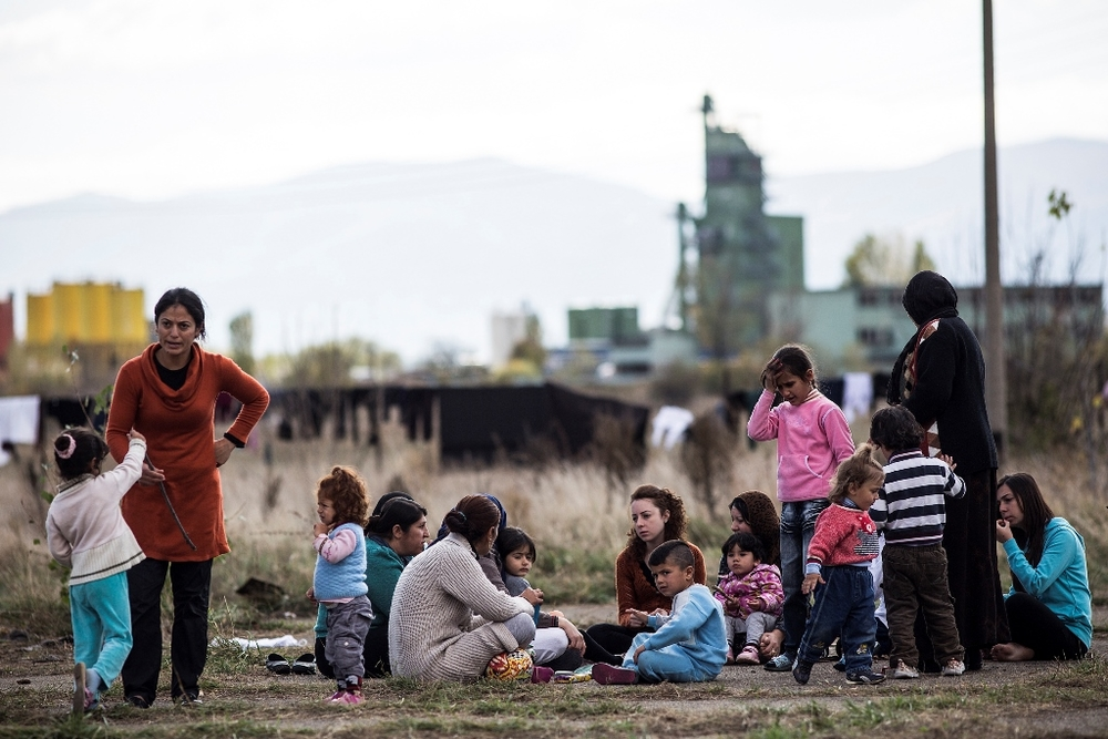 Migrants and asylum seekers, mostly Syrian Kurds, sit in the yard outside a schoolhouse-turned-reception center, known as Vrazhdebna, on the outskirts of the Bulgarian capital Sofia. A massive increase in Syrian new arrivals in recent months has overwhelm