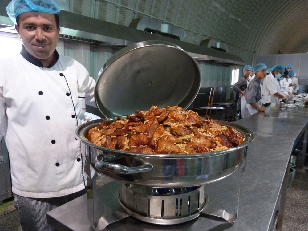 "At the ""five-star"" camp for Syrian refugees in Jordan, run by the United Arab Emirates Red Crescent (UAERC), kitchen staff (in the background) pack rotisserie chicken, flavoured rice and grilled vegetables for refugees  in take-away boxes"