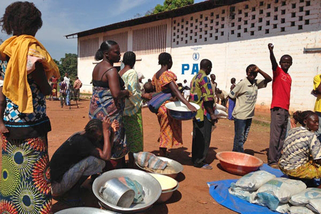 Representatives of displaced families line up at the WFP distribution site in Bossangoa to receive their food rations, which include rice, flour, split peas and cooking oil