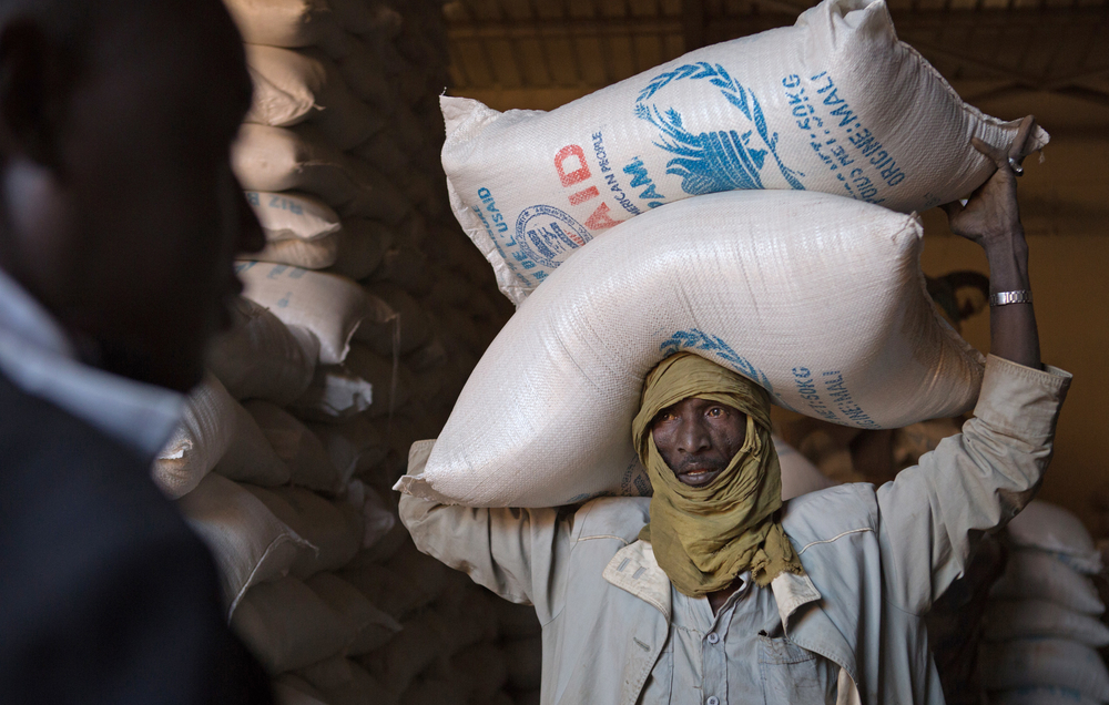 Men unload sacks of rice to store in the World Food Program warehouse in Gao, Mali. The rice is used to respond to emergency food and nutritional needs in conflict-affected areas, such as Gao in northern Mali, which fell under occupation of armed groups i