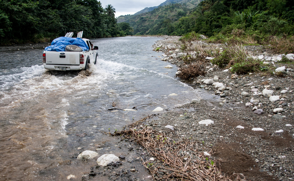 Aid workers with ACTED cross a river during a cholera response mission. Les Cayes, Haiti. (November 2013)