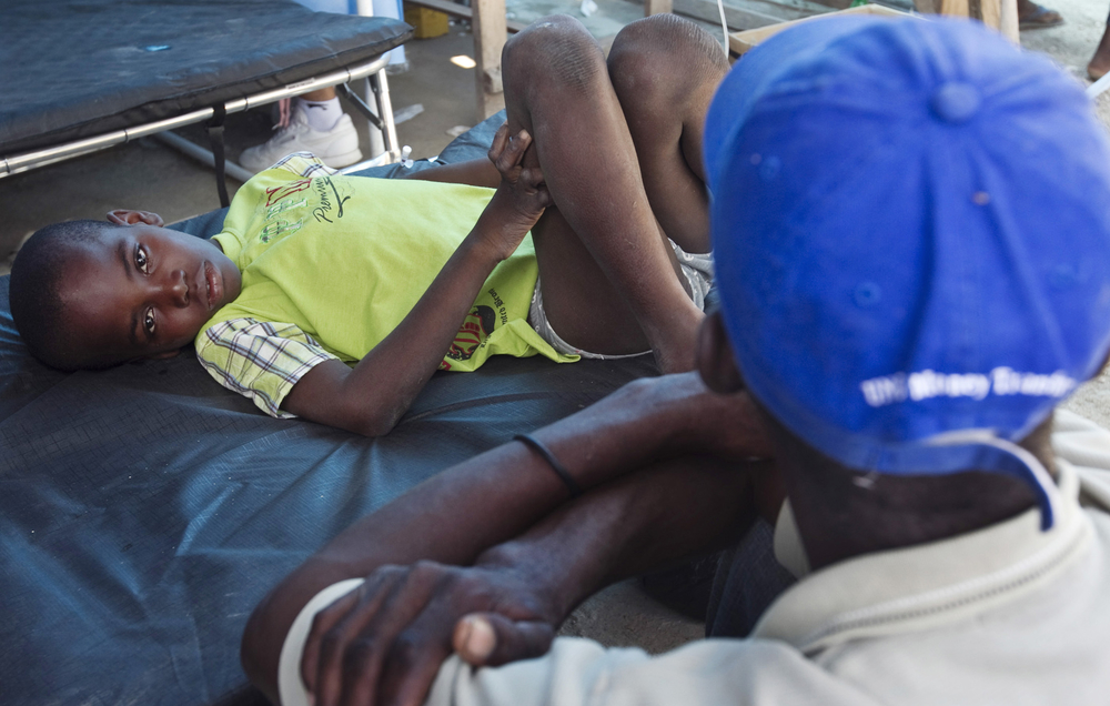 A boy receives treatment for cholera at the hospital in L'Estere, Haiti, as his family watches over him. L'Estere is located in Haiti's Artibonite region, the centre of the recent cholera outbreak.