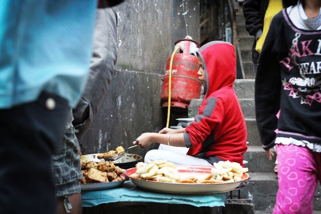 A young Chin refugee cooks traditional Burmese food on a busy street market in Aizawl