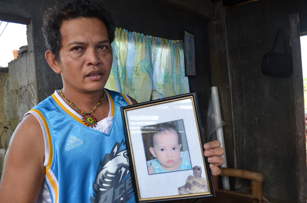 Ferdinand Quieta, 42, and his wife lost all four of their children in the category 5 storm, Typhoon Haiyan, that hit the central Philippines on 8 November. He holds a picture of his five-year-old daughter who has been buried with her siblings in a small p