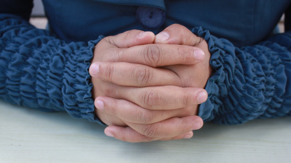closeup of a woman's hands with fingers interlaced and blue sleeves