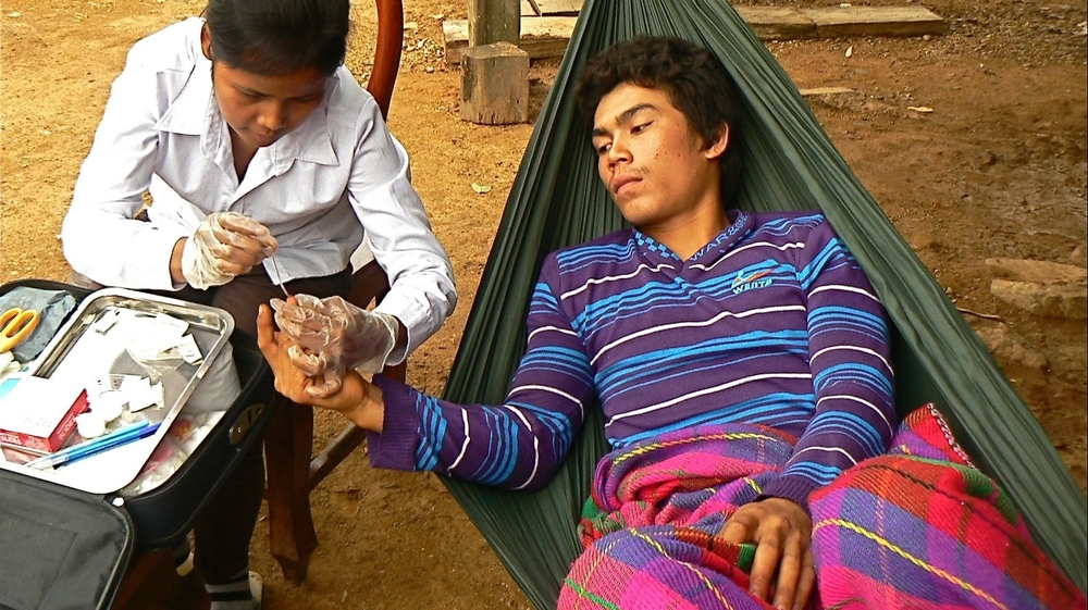 A Village Malaria Worker in Battambang District's Ta Sanh Village in Western Cambodia tests a patient for malaria. Western Cambodia is a hot-spot for artemisinin resistant malaria and Village Malaria Workers or VMWs are the frontline fighters in the war