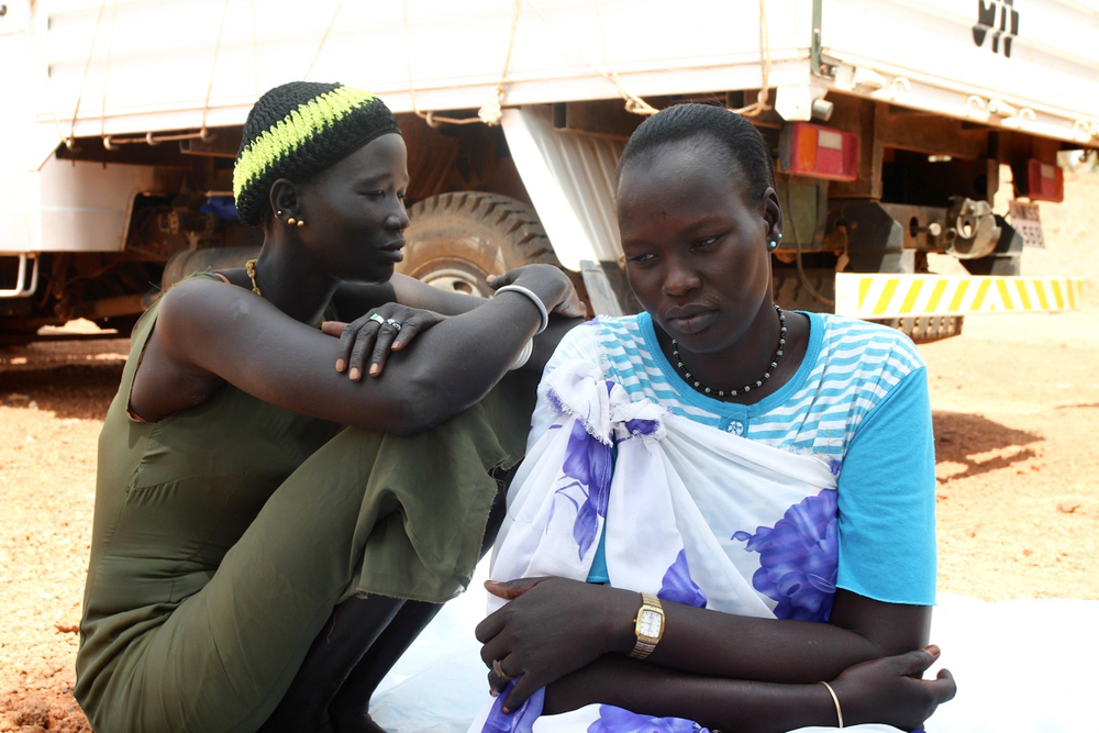 Two women sit at the UNMISS base in Rumbek, Lakes State, South Sudan. 18 February 2014