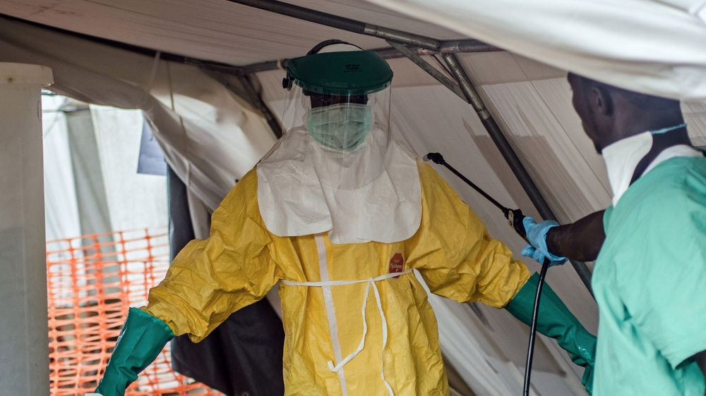 An MSF health worker donning a protective suit to treat Ebola victims in Kailahun, Sierra Leone. July 2014.