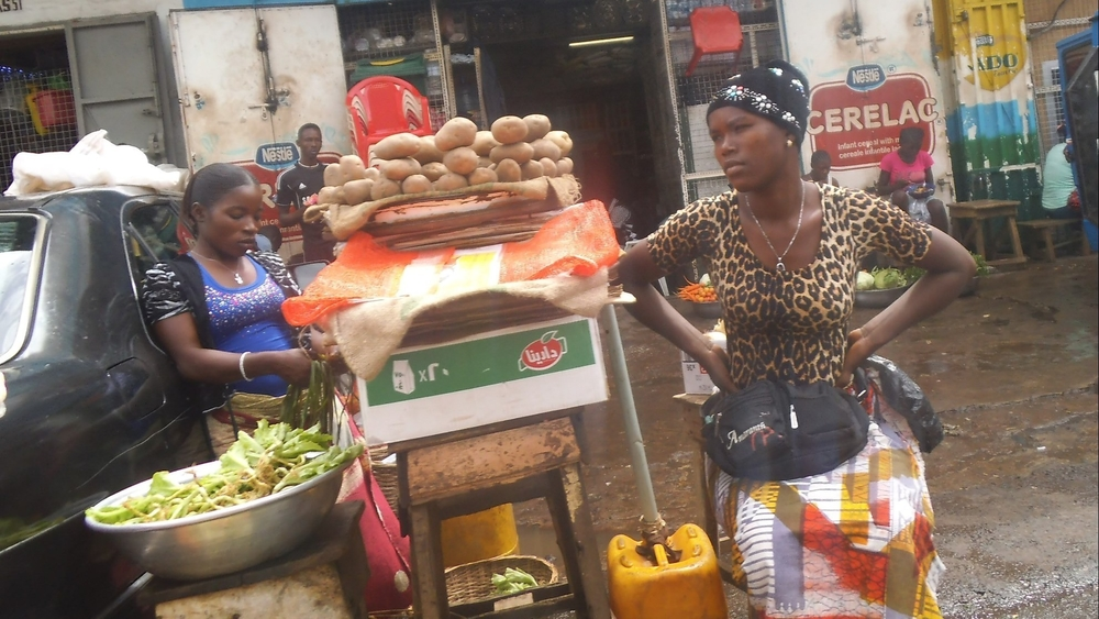 A woman waits for customers in a Freetown market in September 2014. Customer numbers have dropped and food prices risen since Ebola broke out in Sierra Leone earlier this year.