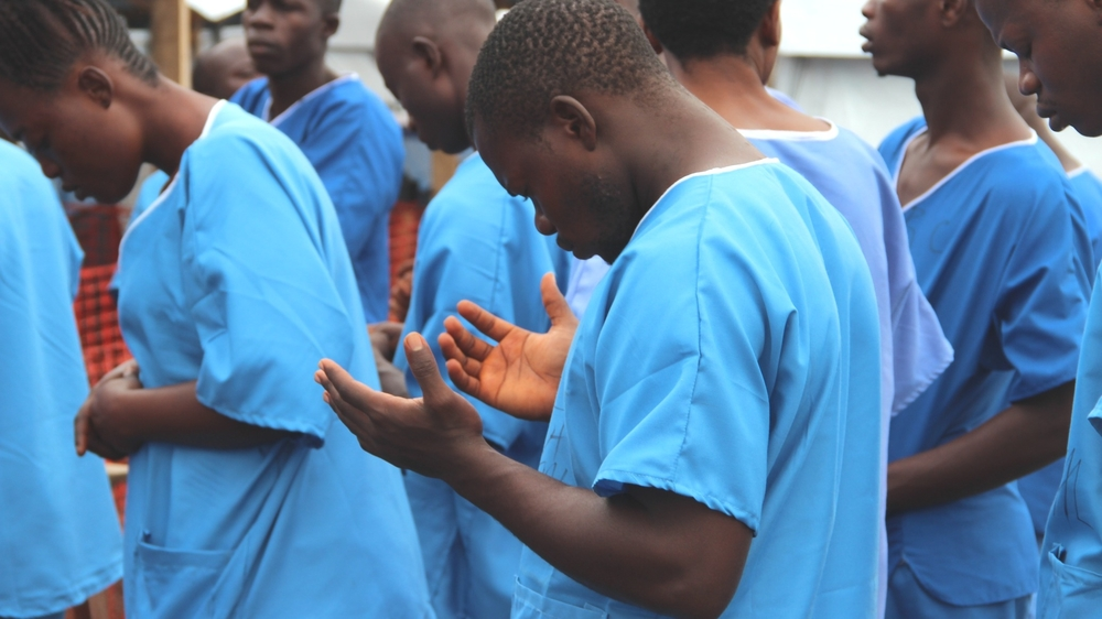Staff at the IFRC Ebola treatment Centre outside of Kenema start the day by praying with the patients.