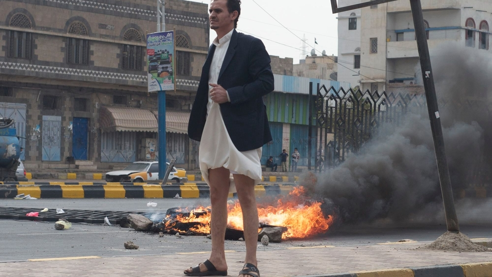 A Yemeni man stands in front of a barricade of burning tyres erected on the main Sixty Metre Road during fuel riots in Sana'a, 30 July 2014