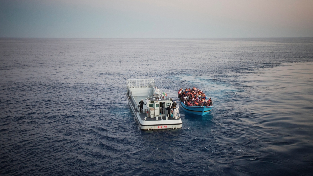 A boat carrying refugees off the coast of Italy in summer 2014 is stopped by the coast guard. Thousands of refugees attempt to make the perilous journey to Europe every year, with hundreds dying. In the summer of 2014 the Mare Nostrum search and rescue te
