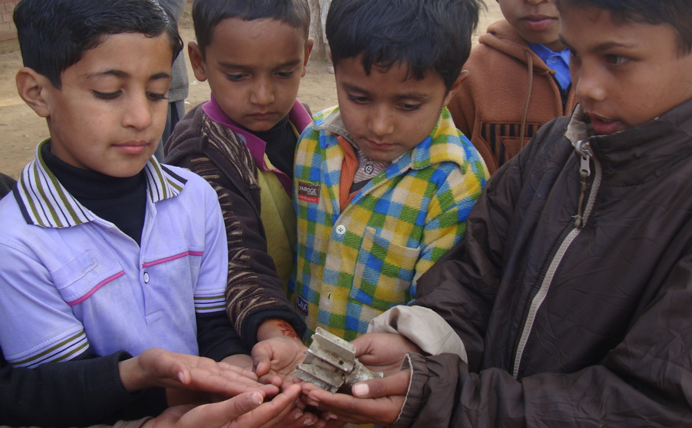 Pakistani children hold the remains of a shell that fell during clashes with India