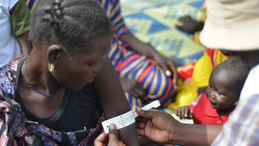 A nutritionist measures a woman's middle upper arm circumference in Fashoda County, South Sudan to see if she is malnourished.