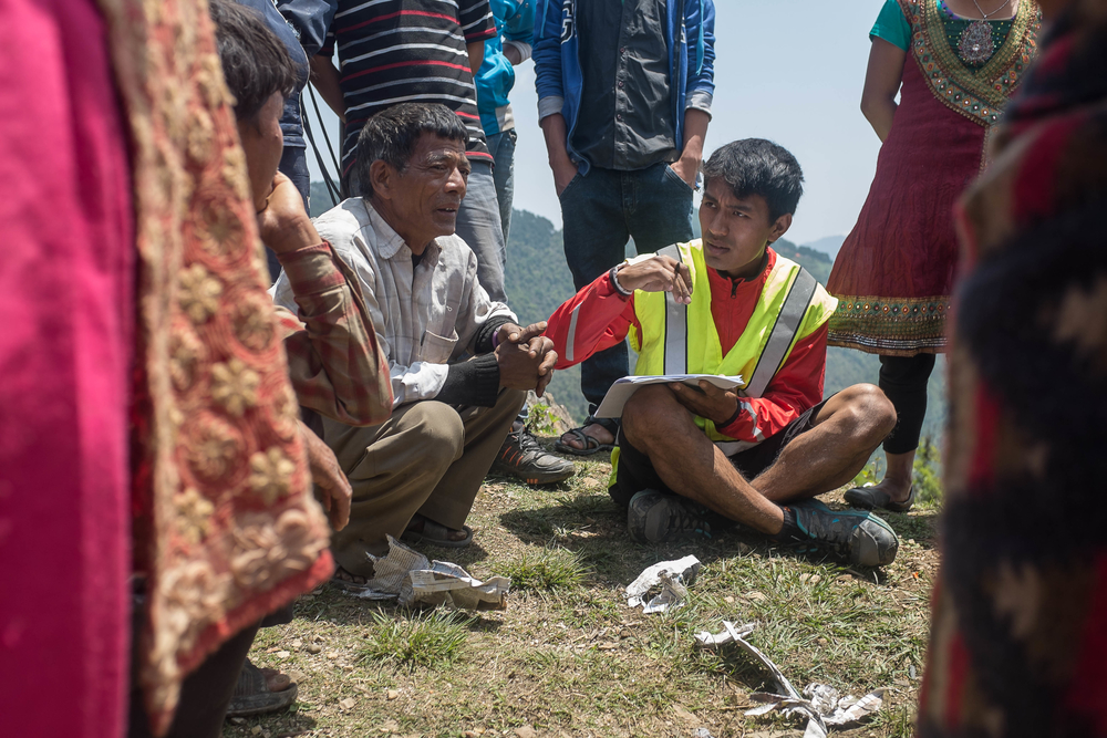A volunteer talks with community members about their situation since the earthquake on 1 May 2015 in Dalchowki, Nepal.