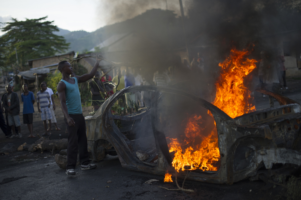 A protestor fuels a burning barricade in the Musaga neighbourhood of Bujumbura, Burundi, on May 4, 2015.