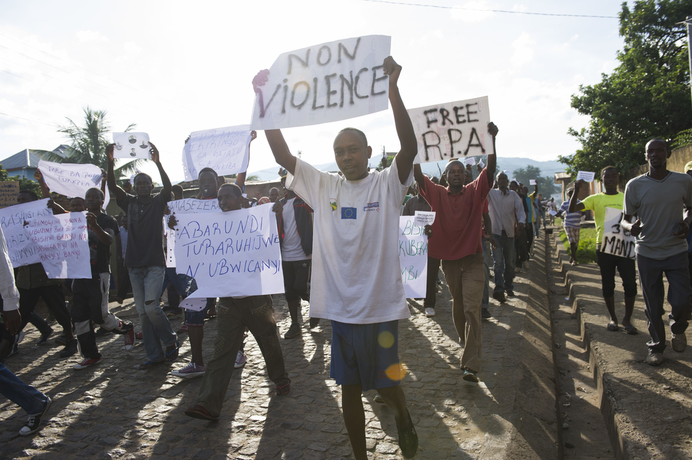 "Protestors demonstrate carrying placards announcing ""no violence"" and ""free RPA"" [Radio Publique Africaine], through the streets of Nyakabiga neighbourhood in Bujumbura on May 4, 2015."