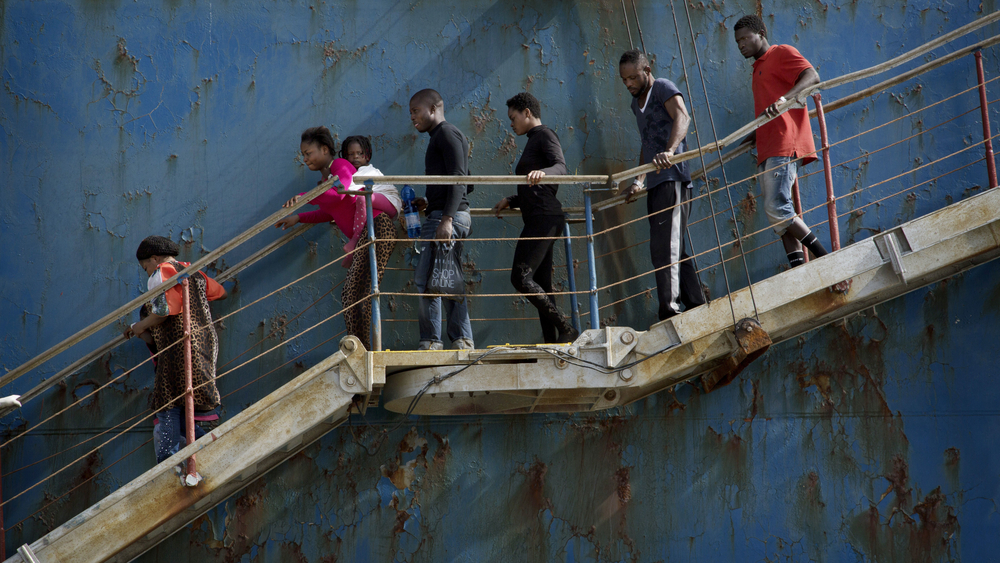 Migrants disembark at the Sicilian port of Catania after being rescued from a shipwreck by a merchant vessel on 5 May, 2015