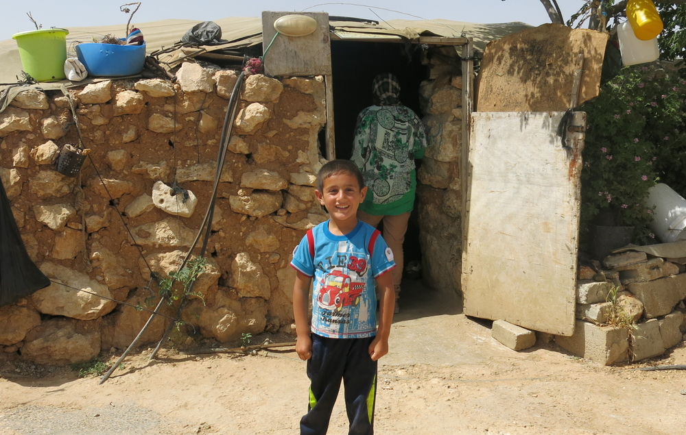 A Palestinian child stands in front of his home in the village of Susiya, in the West Bank. The village is due to be destroyed in the coming weeks