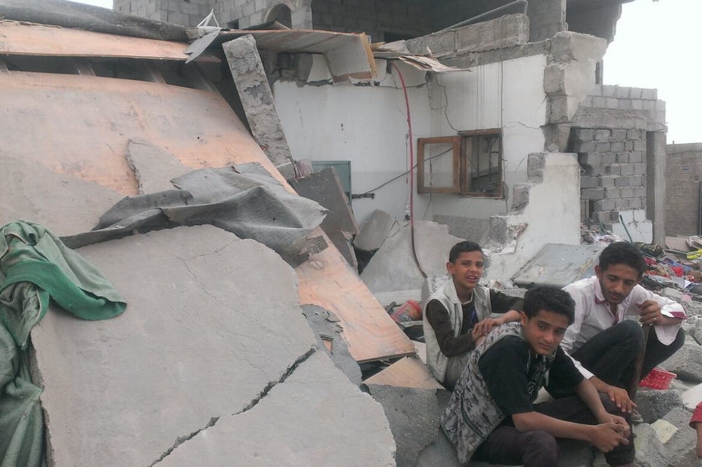 Three Yemenis sit outside destroyed homes, shortly after an airstrike by the Saudi Arabian-led coalition. The attack came a day after a humanitarian truce failed to take hold.