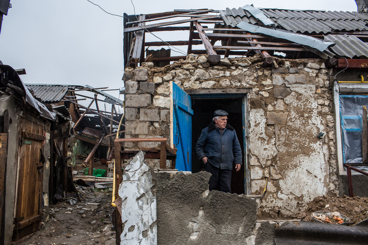Ivan Kubarev, 61, shows the destroyed home of his elderly relatives in Triokhizbenka, who are now sheltering with him and his wife nearby.