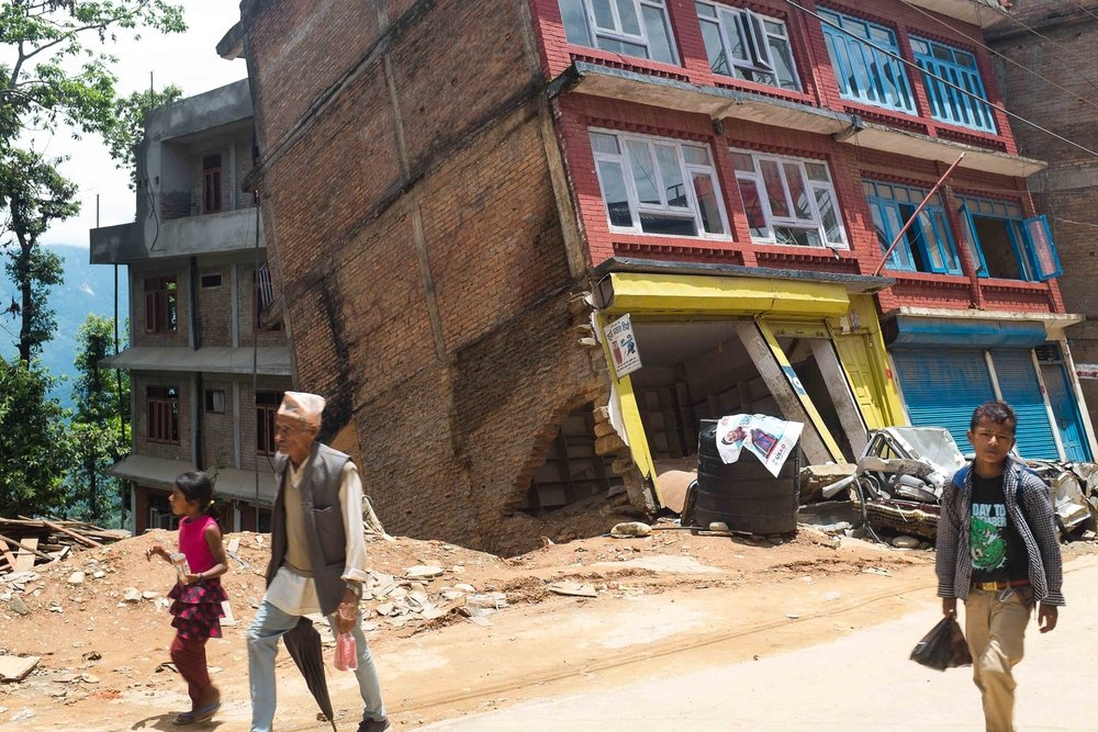 Residents walk past a building damaged during the earthquake in the city centre in Chautara, Nepal, on 8 July 2015