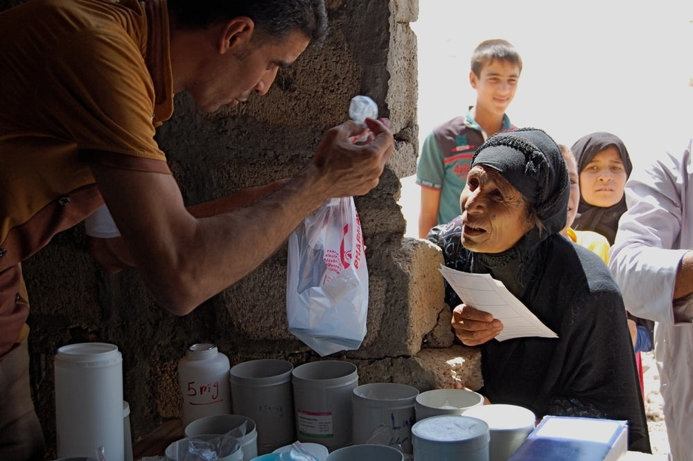 In Sankur village, southern Kirkuk, IDP Garha Mahmoud collects her medication from Elfan, an MSF drugs dispenser.