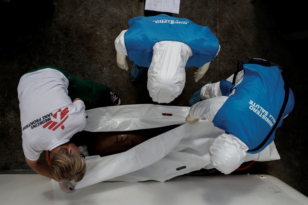 A Medecins Sans Frontiers doctor and Italian officials examine the body of a 15-year-old Somali boy who died on board MSF's Dignity 1 ship after being rescued at sea.