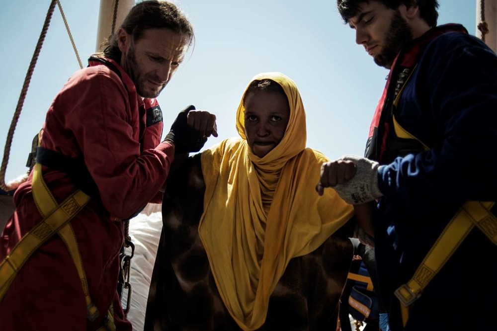 A pregnant Somali woman is helped onto the MSF boat, Dignity 1, after being rescued at the sea on August 23, 2015