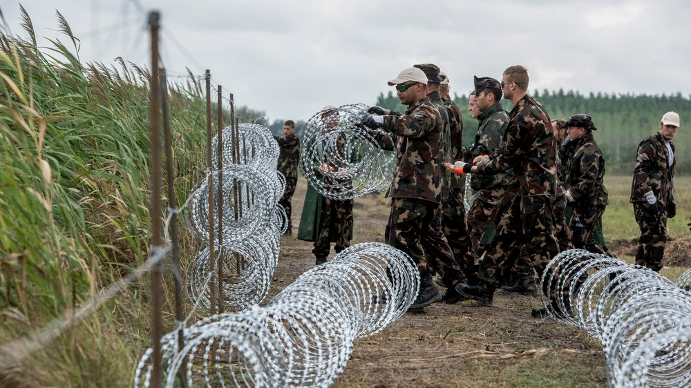 Hungarian soldiers constructing a fence at Hungary's border with Serbia where 155,000 migrants and refugees entered the country between January and September, 2015.